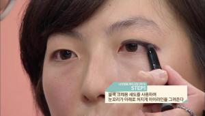 민아의 메이크업 포인트는 블랙 아이라인과 섀도로 스머지한 귀여운 느낌의 눈매 연출이에요<br><br> 1. 블랙 크레용 섀도를 사용하여 눈꼬리가 아래로 처지게 아이라인을 그려주세요 <br><br><b>TIP</b> 눈꼬리를 살짝 내려 눈매가 부드러워지는 효과를 주세요